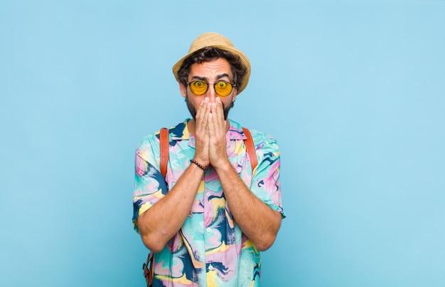 Молодой бородатый турист, чувствующий себя обеспокоенным, расстроенным и напуганным, прикрыв рот руками, выглядел обеспокоенным и испортил Premium Фотографии