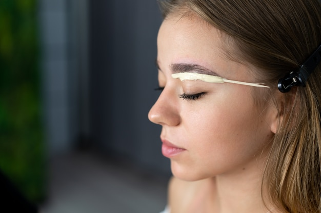 Young beautician caucasian girl holds model eyebrow correction Premium Photo