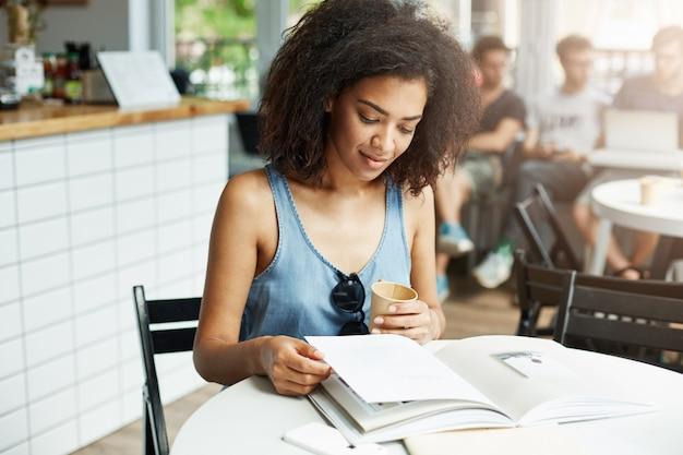 Молодой красивый африканский студент женщины сидя в кафе усмехаясь смотрящ кассету выпивая кофе. обучение и воспитание. Бесплатные Фотографии