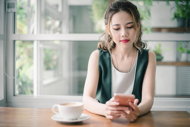 Young beautiful asain lady touching and browsing her smart phone at home. Premium Photo