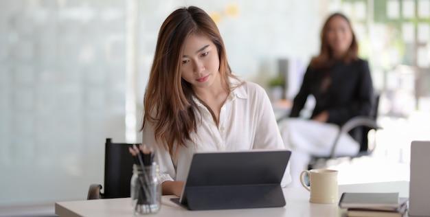 Молодая красивая азиатская коммерсантка работая над ее проектом с таблеткой Premium Фотографии