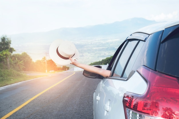 Young beautiful asian girl holding hat weave and reach out of the car at sunset Premium Photo