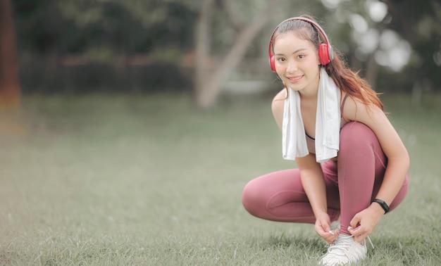 ヘッドフォンの靴ひもを結ぶと実行する準備をして、笑顔でカメラ目線の若い美しいアジアスポーツウーマン。 Premium写真