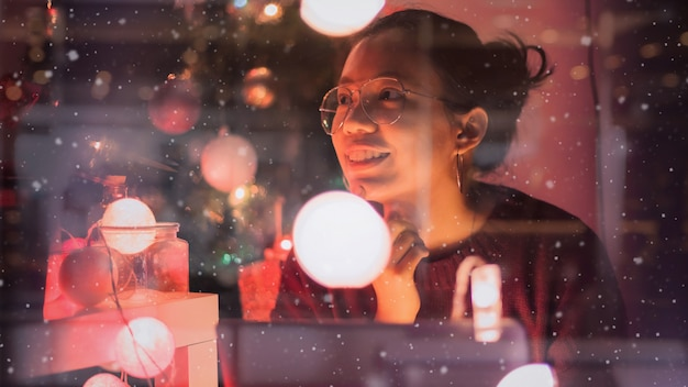 Young beautiful asian woman feel good with the new year celebrations with gift box in home decorate with christmas tree.concept of happy holidays.glass window reflection and snow effect. Premium Photo