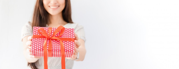 Young beautiful asian woman holding gift box in hand. Premium Photo