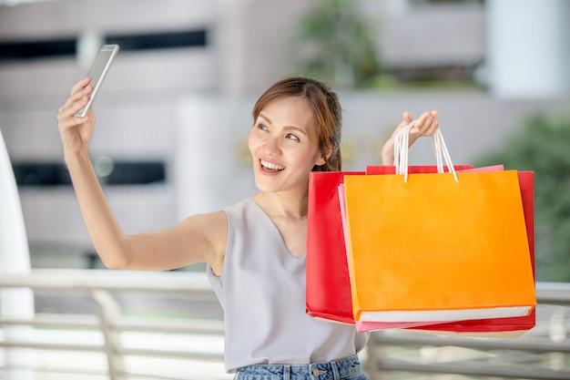 Молодая красивая азиатская женщина держа ее smartphone к делать selfie с ее хозяйственными сумками на улице города Premium Фотографии