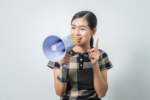 スピーカー、黒い髪を保持している若い美しいアジアの女性。 Premium写真