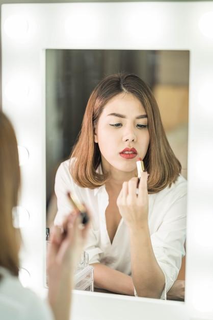 Young beautiful asian woman making make-up near mirror Premium Photo