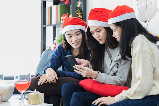 Young beautiful asian woman selfie with smartphone and celebration with best friend.smiling face in room with christmas tree decoration for holiday festival.christmas party and celebration concept. Premium Photo