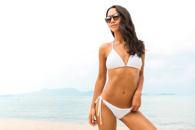 Young beautiful asian woman in white biniki at the beach in summer Premium Photo