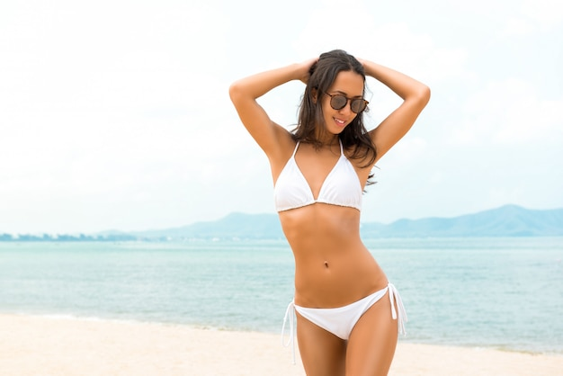 Young beautiful asian woman in white biniki at the beach in summer Premium Photo