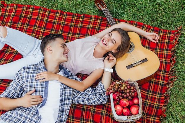 彼女の男の子が毛布のカーペットの上に座って、すべての瞬間を楽しんでいる若い美しい魅力的な女の子 Premium写真