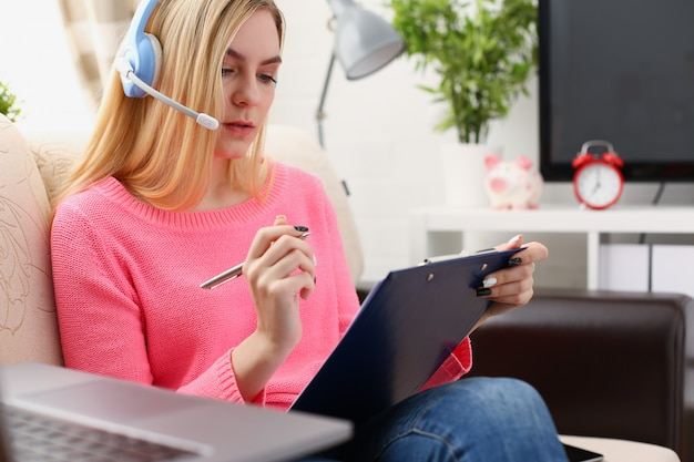 ラップトップで音楽を聴くと、腕の中で若い美しいブロンドの女性がリビングソファのソファに座ってバインダーを保持します。 Premium写真