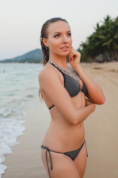 Молодая красивая блондинка женщина, загорающая на песчаном пляже в купальном костюме бикини, старинное ожерелье Бесплатные Фотографии