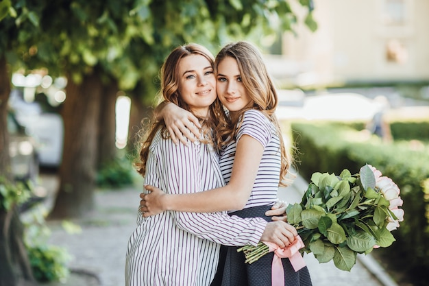 Young beautiful blonde daughter hugs her middle-aged mom on the streets of the city. they are happy and love each other. Premium Photo