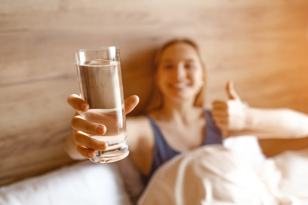Young beautiful blonde woman sitting in bed in morning. she hold gass of water in hands and big thumb up. beautiful smile. Premium Photo