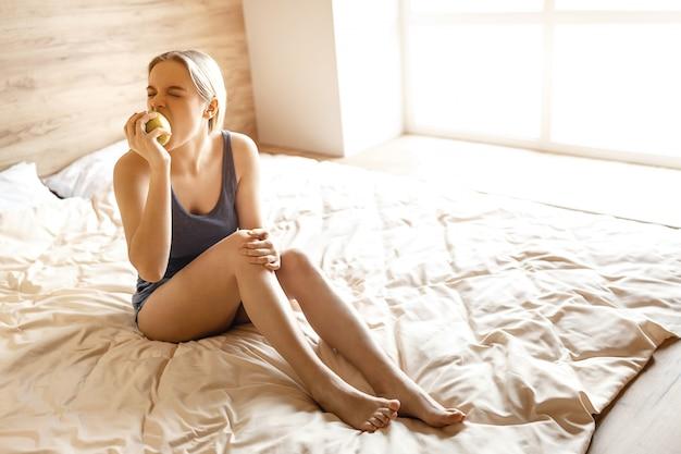 Молодая красивая белокурая женщина сидя в кровати в утре. модель кусает яблоко и смотрит в сторону. она сконцентрировалась на еде яблока. дневной свет. Premium Фотографии