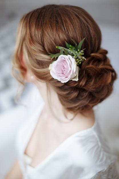 Молодая красивая прическа невесты с живыми цветами. Premium Фотографии