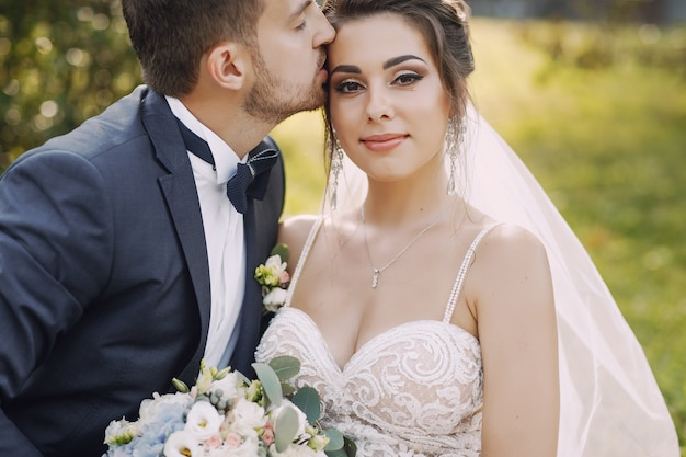A young and beautiful bride and her husband standing in a park with bouquet of flowers Free Photo