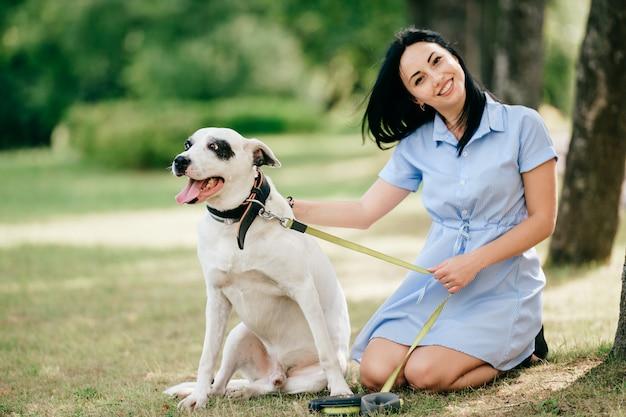 青いドレスの若い美しいブルネット陽気な少女は、自然で屋外彼女の男性の白い犬と一緒に遊んで楽しい時を過します。素敵な女性は親切なペットを愛しています。 Premium写真