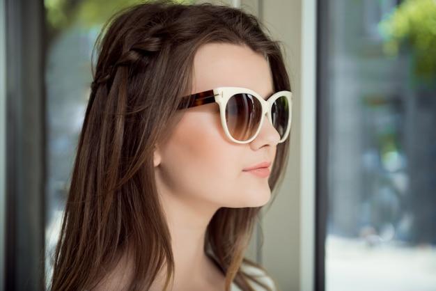 眼鏡店で買い物をしながらスタイリッシュなサングラスを試着して自信を持って表現を持つ若い美しいブルネット 無料写真