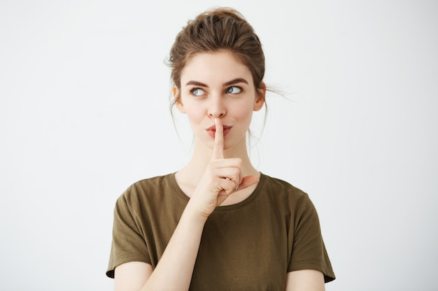 お団子を示す若い美しいブルネットの女性は沈黙を保つ 無料写真