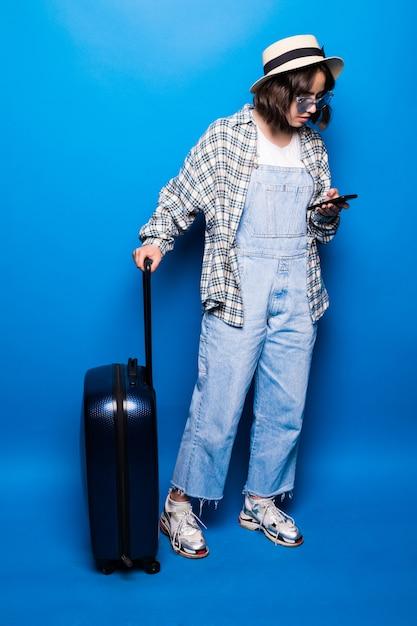 La giovane bella bruna scrive il messaggio di testo accanto alle sue valigie isolate Foto Gratuite