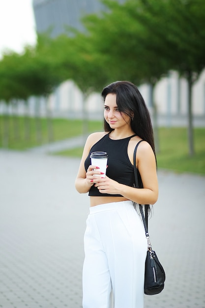 Young beautiful business woman drinks coffee near beside office building Premium Photo