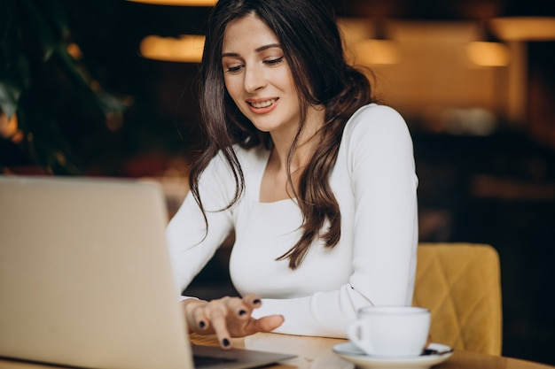 Young beautiful business woman working on computer in a cafe Free Photo