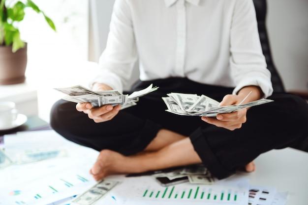 Молодая красивая деловая женщина держит деньги, сидя на столе на рабочем месте. Бесплатные Фотографии