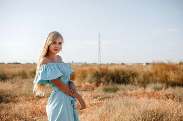 Young beautiful caucasian blonde girl in light blue dress stands on the field with the sun-scorched grass Premium Photo
