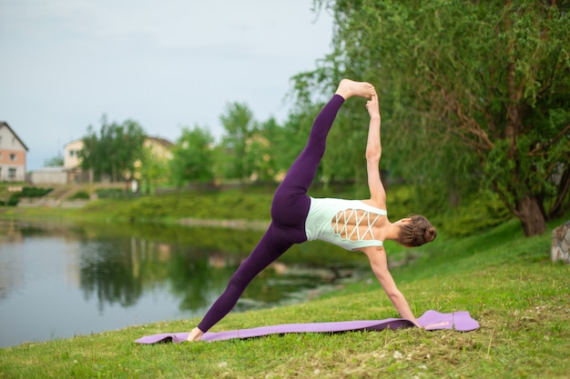 Young beautiful caucasian brunette girl doing yoga on a green lawn against the background of the river Premium Photo