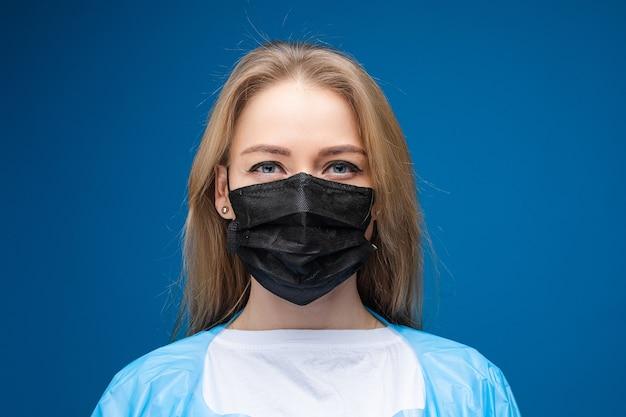 파란색 의료 가운과 그녀의 얼굴에 흰색 의료 마스크와 젊은 아름 다운 백인 여성은 카메라에 보이는 무료 사진