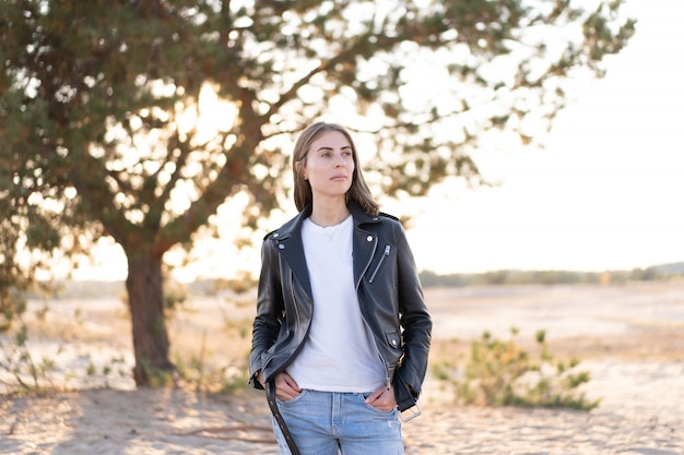 Young beautiful caucasian woman dressed leather jacket and jeans stands on the beach the rays of the sun break through the foliage of a tree Premium Photo