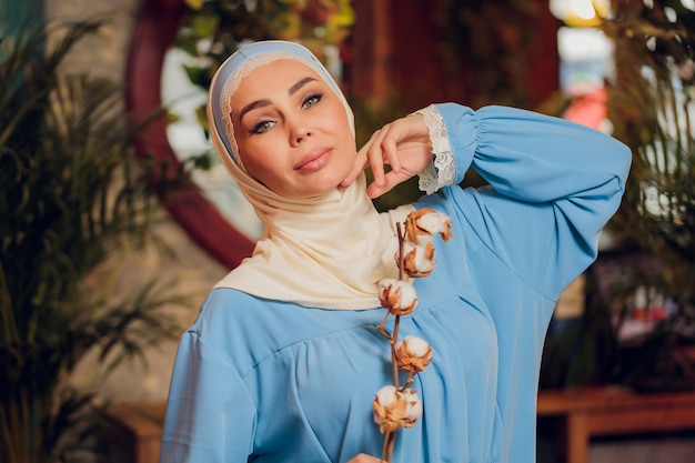 Young beautiful caucasian woman wearing traditional muslim headscarf in hipster coffee shop with big full length windows. female in blue hijab at cozy cafe. background, copy space, close up portrait. Premium Photo