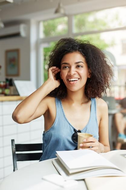 Сидеть молодого красивого жизнерадостного африканского студента женщины усмехаясь смеясь над в кафе. книги журналов лежат на столе. обучение и воспитание. Бесплатные Фотографии