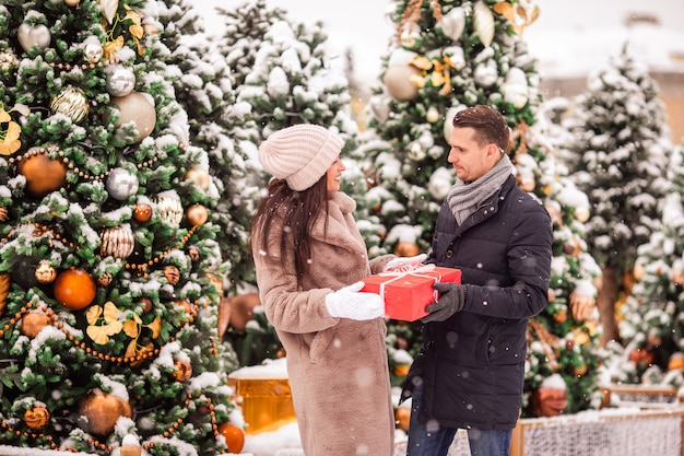 Young beautiful cheerful couple celebrating christmas in the city street and giving gift to each other. Premium Photo