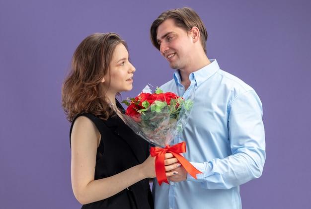 파란색 벽 위에 서있는 발렌타인 데이를 축하 그의 웃는 사랑스러운 여자 친구에게 빨간 장미 꽃다발을주는 젊은 아름 다운 부부 행복한 사람 무료 사진