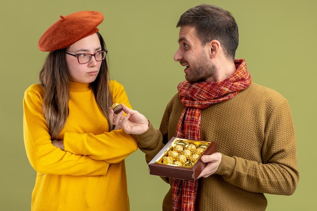 緑の壁の上に立っているバレンタインデーを祝うベレー帽で彼の気分を害したガールフレンドにチョコレート菓子を提供する若い美しいカップル幸せな男 無料写真
