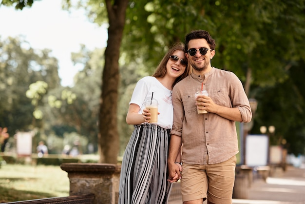 Young beautiful couple have a fun and walking on city streets and drinking coffee Premium Photo