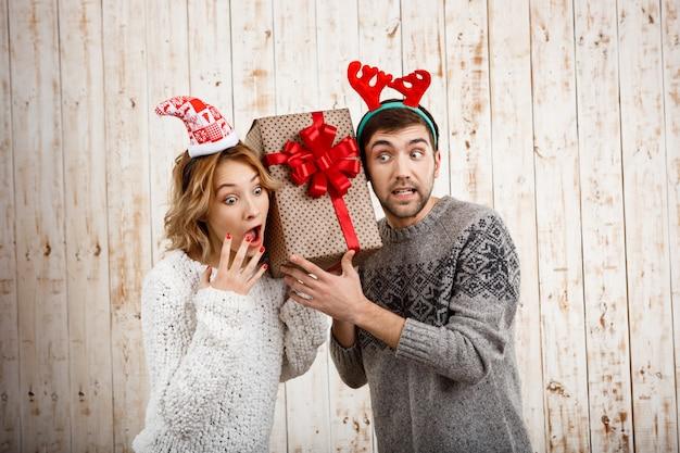 나무 벽에 크리스마스 선물을 들고 젊은 아름 다운 부부 무료 사진