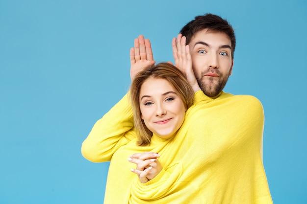 青い壁を越えて楽しんで笑ってポーズ1つの黄色いセーターの若い美しいカップル 無料写真