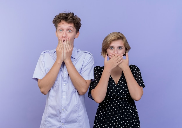 젊은 아름 다운 부부 남자와 여자 손으로 입을 덮고 파란색 벽 위에 서 충격을 받고 무료 사진