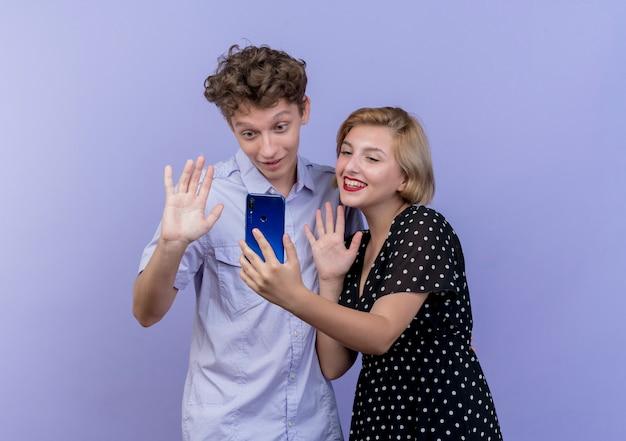 若い美しいカップルの男性と女性が手で手を振って、青に笑みを浮かべてビデオ通話を持っています 無料写真
