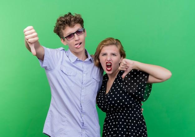 Giovane bella coppia uomo e donna dispiaciuto che mostra i pollici verso il basso in piedi sopra la parete verde Foto Gratuite