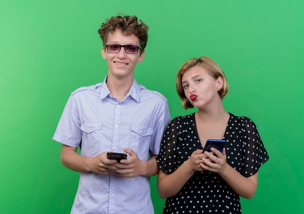 Giovane bella coppia uomo e donna che tengono smartphone sorridente in piedi sopra la parete verde Foto Gratuite