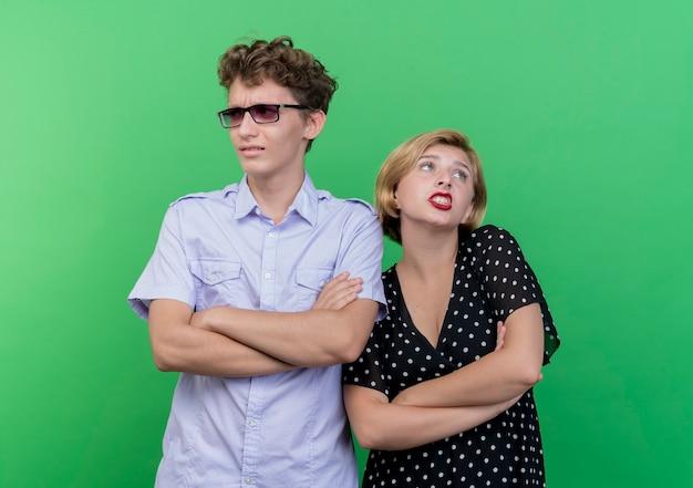 Giovane bella coppia uomo e donna in piedi uno accanto all'altro guardando confuso in piedi sopra la parete verde Foto Gratuite