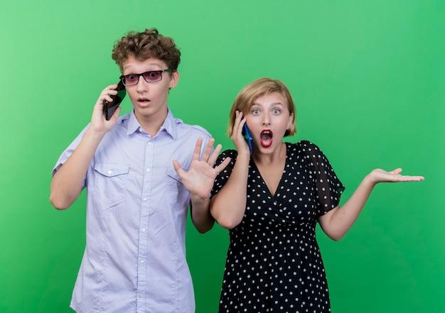Giovane bella coppia uomo e donna che parla sui telefoni cellulari alla ricerca confusa e incerta in piedi sopra la parete verde Foto Gratuite