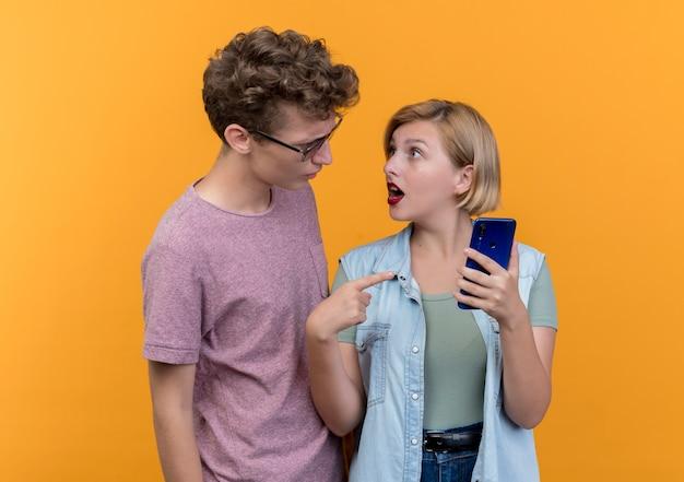 Giovane bella coppia uomo e donna che indossa abiti casual uomo litigando con la sua ragazza con lo smartphone in piedi sopra la parete arancione Foto Gratuite