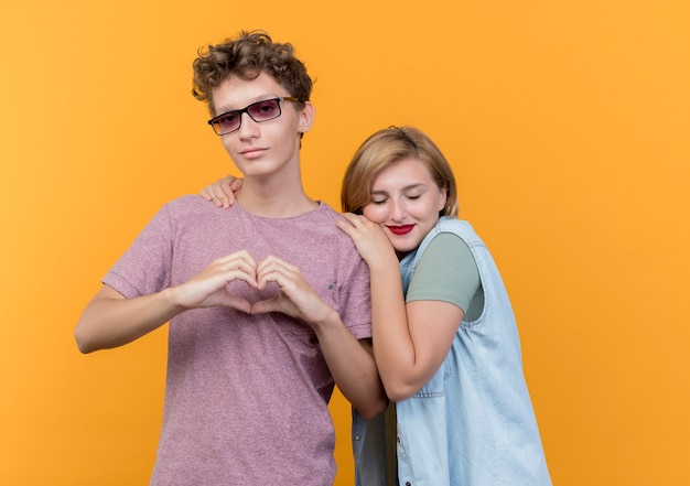 Giovane bella coppia uomo e donna che indossa abiti casual in piedi insieme uomo che mostra il gesto del cuore mentre il suo amico appoggiato la testa sulla sua spalla sopra la parete arancione Foto Gratuite